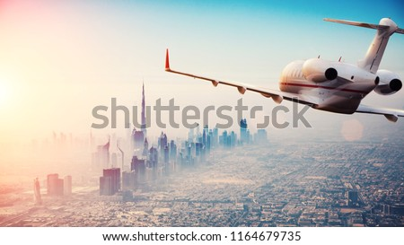 Private jet plane flying above Dubai city in beautiful sunset light. Modern and fastest mode of transportation, business life. #1164679735