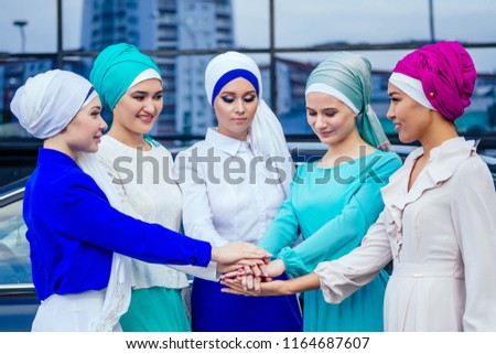 a group of five young and attractive business women in Muslim dress multi-colored hijab and a turban covering the head working thumbs up stacking hands puts palm together on the centre team work #1164687607