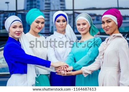 a group of five young and attractive business women in Muslim dress multi-colored hijab and a turban covering the head working thumbs up stacking hands puts palm together on the centre team work #1164687613