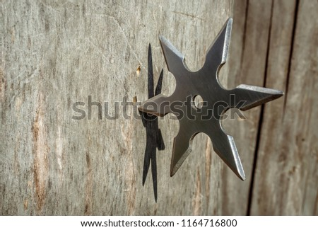 Shuriken (throwing star), traditional japanese ninja cold weapon stuck in wooden background #1164716800