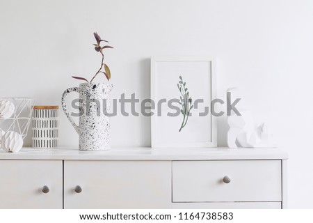 Creative cupboard with mock up poster frame, cat figures, pink flower in stylish vase and books. Modern and minimalistic concept of shelf.