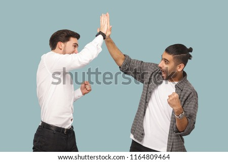 Yes we did. expression profile side view of two young handsome happy satisfied bearded partner celebrating triumph together, giving hi five hands. indoor studio shot, isolated on light blue background #1164809464