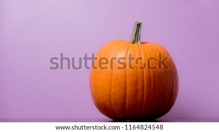 one orange pumpking on table with purple background #1164824548