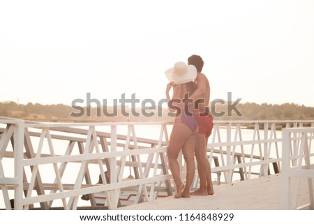 beautiful young couple embraced enjoying sunset on the hotel jetty #1164848929