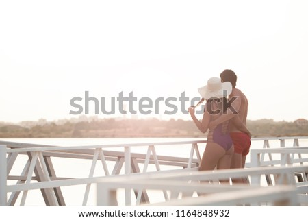 beautiful young couple embraced enjoying sunset on the hotel jetty #1164848932