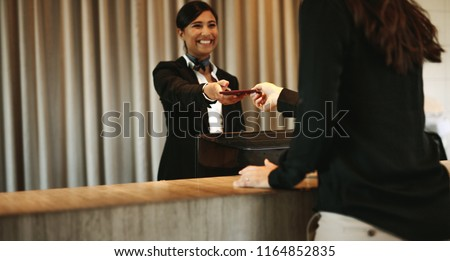 Smiling female concierge returning the documents to hotel guest after check-in process. Female client receiving her documents at hotel reception desk after check-in. #1164852835
