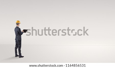 Young architect with construction helmet standing in an empty space and holding a plan #1164856531