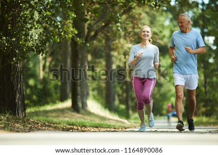 Active and healthy aged couple running in natural environment on summer morning Royalty-Free Stock Photo #1164890086