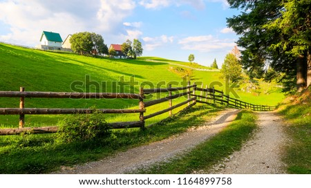 Wooden Fence and Countryside Road in Bosaca Village on Durmitor Mountain in Montenegro #1164899758