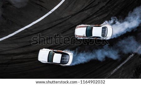 Aerial top view two cars drift battle on race track, Two race cars view from above, Car drifting, Race drift car with lots of smoke from burning tires on speed track. #1164902032