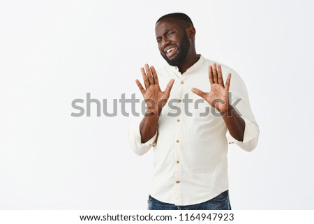 Please leave me alone. Portrait of displeased and bothered careless african american businessman with beard in white shirt, raising palms in no or stop gesture, turning away with grimace of dislike #1164947923