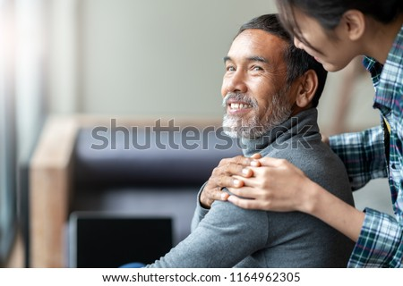Smiling happy older asian father with stylish short beard touching daughter's hand on shoulder looking and talking together with love and care. Family relationship with bond and care concept. #1164962305