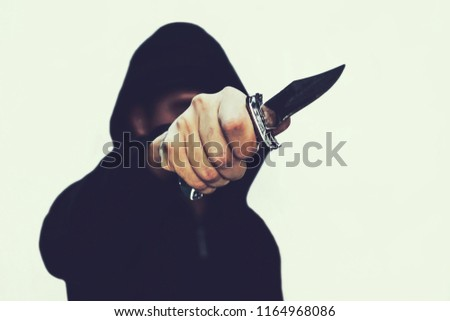 photo of a hooded man with a knife. A prisoner with a Shiv. The threat of a cold weapon. A terrorist from ISIS on a white isolated background #1164968086