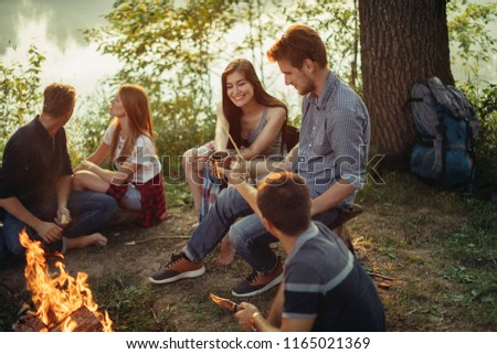 guy is sharing drink with beautiful cheerful girl while sitting around the bonfire. man is looking after the woman #1165021369