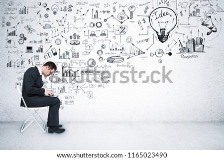 Side view of young businessman sitting on chair in interior with business sketch. Success and education concept  #1165023490