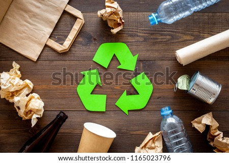 Recycling. Green recycle eco symbol. Recycled arrows sign near matherials for recycle and reuse on dark wooden background top view #1165023796