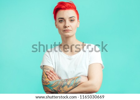 serious emo girl isolated over blue wall background with arms crossed. Looking at the camera.