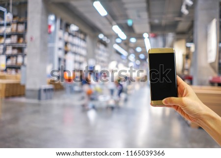 Hands holding mobile phone with shopping mall or department store  blurred background and bokeh light #1165039366