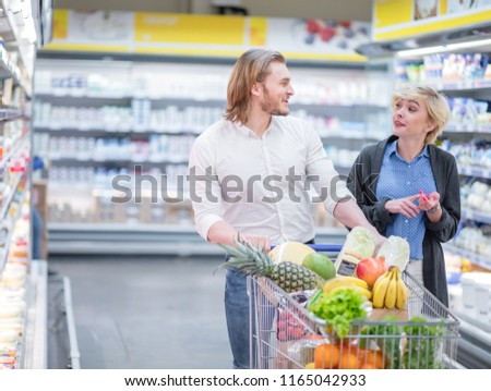 Couple in a supermarket shopping equipped with a shopping cart buying groceries and other stuff, they are looking for what they need #1165042933