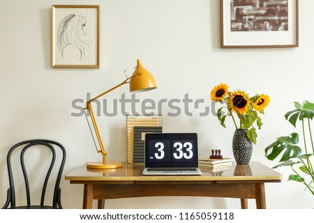 Sunflowers, yellow lamp and laptop on wooden desk in home office interior with posters. Real photo #1165059118