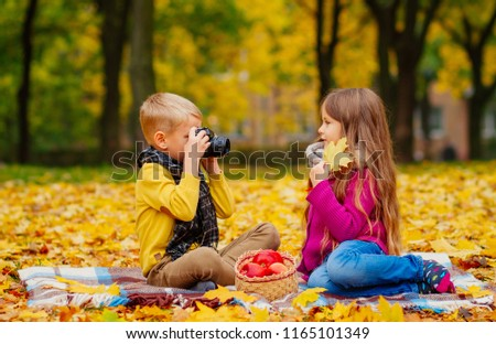 children play in nature, children in the autumn park have fun and take pictures, a little boy and a girl in yellow leaves