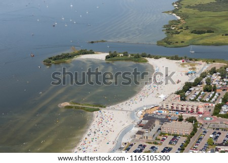 Aerial view Dutch village Makkum in Friesland with beach and swimming people #1165105300