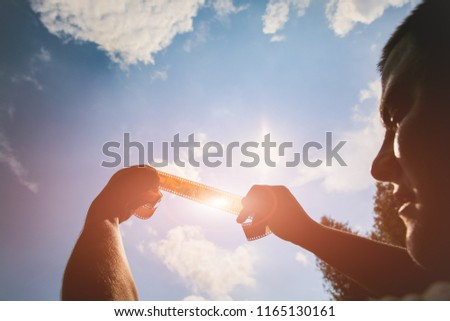 Man is holding film strip in his hands against the sunlight and sky. Guy remembering his childhood memories in the nature. Retro concept on the photo tape. #1165130161
