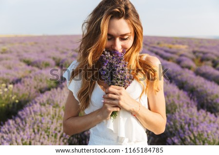 Photo of caucasian young woman in dress holding bouquet of flowers while walking outdoor through lavender field in summer #1165184785