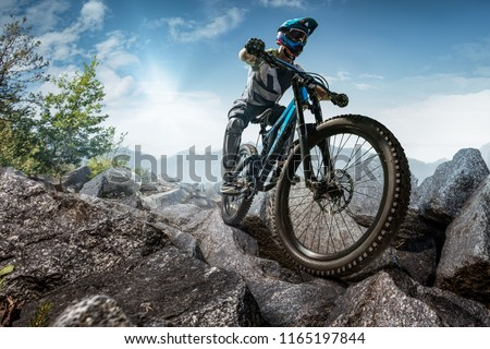 Mountain biker on stone forest trail. Male cyclist rides the rock #1165197844