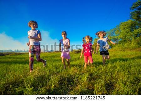 Group of happy kids running in green summer field #1165221745