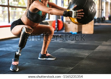 Portrait of beautiful invalid woman with prosthesis in tracksuit doing sit-ups with fitness ball in gym #1165231354