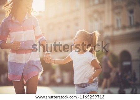 Lots of laughs when they're together. Mother and daughter holding hands and running on city street. Close up. Copy space. #1165259713