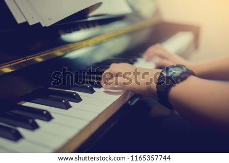 selective focus to hands of boy put black watch to play the piano with music notation.  There are musical instrument for learning music. #1165357744