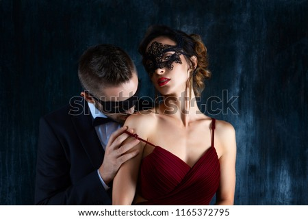 Rich millionaire man male in black carnaval mask bow tie and suit seduces tempts lures woman female in expensive red evening dress. Sex, tempts, harassment, sexism, seduction, henpecked issues #1165372795