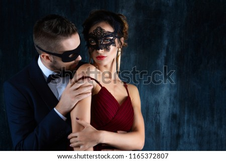 Rich millionaire man male in black carnaval mask bow tie and suit seduces tempts lures woman female in expensive red evening dress. Sex, tempts, harassment, sexism, seduction, henpecked issues #1165372807