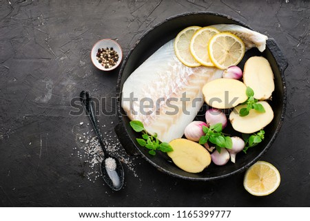 Cod fillets with fresh potatoes, shallots, basil, lemon in a black cast-iron frying pan on a dark background before cooking. Top View #1165399777
