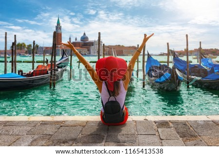 Happy traveller woman sits in front of the traditional gondolas of St. Mark's Square in Venice, Italy Royalty-Free Stock Photo #1165413538