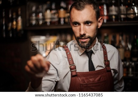 Smiling bartender in the white shirt and brown leather apron holding a transparent cocktail in the martini glass on the bar counter on focus #1165437085
