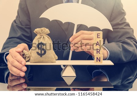 Disability income protection insurance or IPI concept : Businessman holds a white umbrella protects dollar bag on a seesaw / balance scale, IPI is an insurance policy paying benefits to policyholders. #1165458424