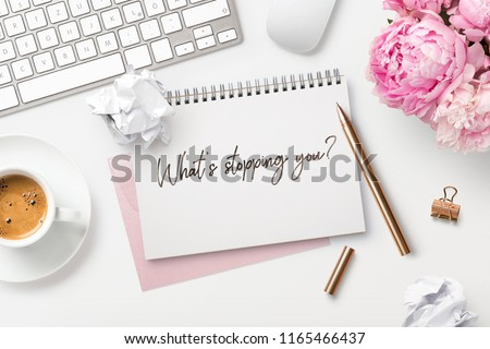 What's stopping you? Feminine workspace with bunch of peonies in a vase, computer, writing supplies, paper balls and a cup of coffee and hand-written quote on a white desk. Business concept. Flat lay. Royalty-Free Stock Photo #1165466437
