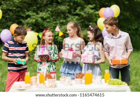 holidays, childhood and celebration concept - happy kids with gifts on birthday party at summer garden #1165474615