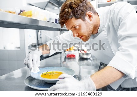 food cooking, profession and people concept - happy male chef cook serving and cleaning plate of soup at restaurant kitchen Royalty-Free Stock Photo #1165480129
