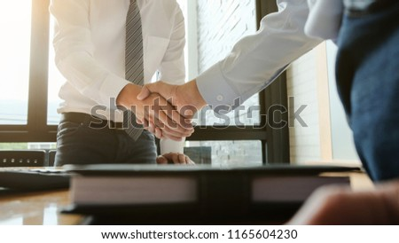 Two confident business man partner shaking hands in meeting room #1165604230