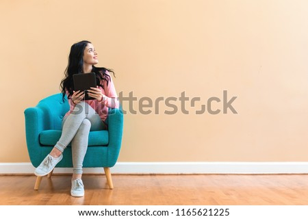 Young woman using her tablet on a blue chair Royalty-Free Stock Photo #1165621225