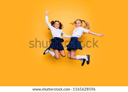 Achievements concept, dynamic images. Full length, legs, body, size portrait of carefree, careless, small girls jumping isolated on yellow background raised fists up Royalty-Free Stock Photo #1165628596