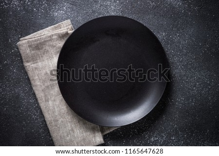 Black plate, cutlery and napkin on stone table top view. Table setting. #1165647628