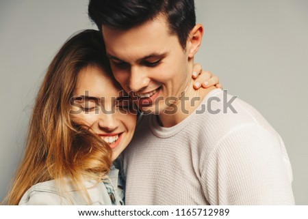 Portrait of beautiful young couple in casual clothes hugging and smiling, on gray background #1165712989