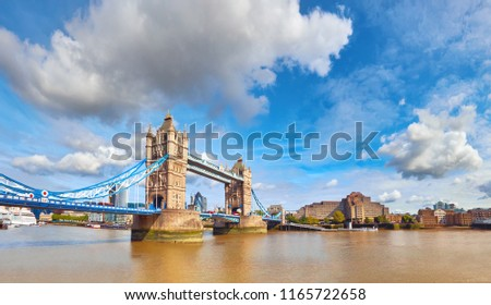 Tower Bridge in London on a bright sunny day under gorgeous sky with clouds. Panoramic image of riverside with the bridge.