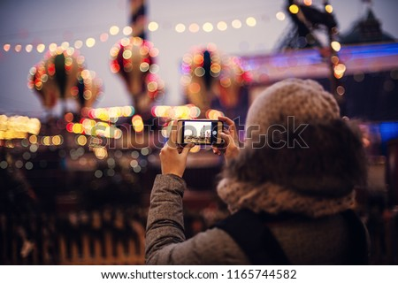 Woman Taking Pictures of European Christmas Market Scene on Smartphone. Girl Enjoying Winter Holiday Season, visiting Outdoors Christmas Market.