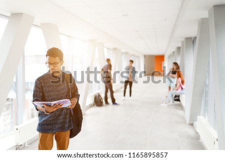 A student from India stands with a book at the University. Students in the background. The photo illustrates education, College, school, or University. #1165895857